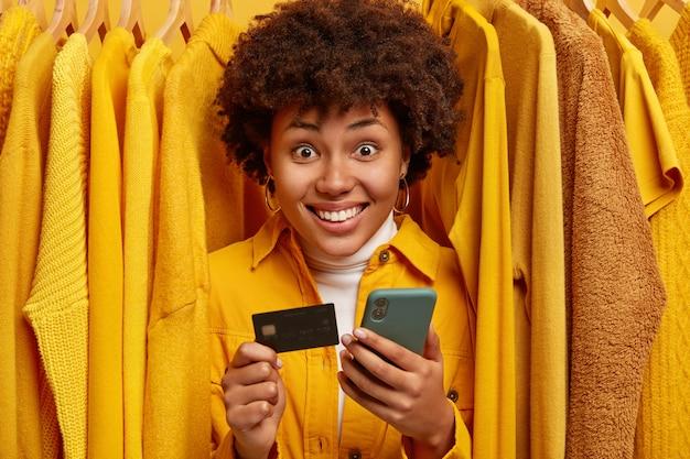 Positieve mixed race shopaholic staat in de buurt van rek met kleding, gebruikt creditcard en smartphone om aankopen te doen