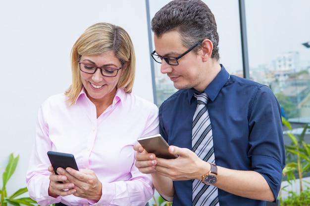 Positieve moderne bedrijfscollega's in oogglazen die gadgets gebruiken