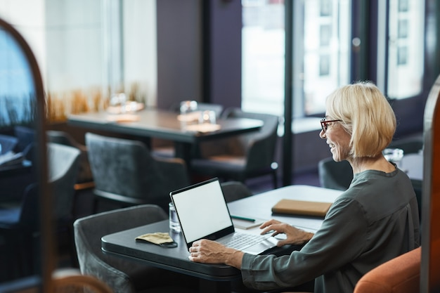 Positieve moderne volwassen zakenvrouw in glazen zittend aan tafel in café met wifi en praten via videoconferentie-app tijdens het gebruik van laptop