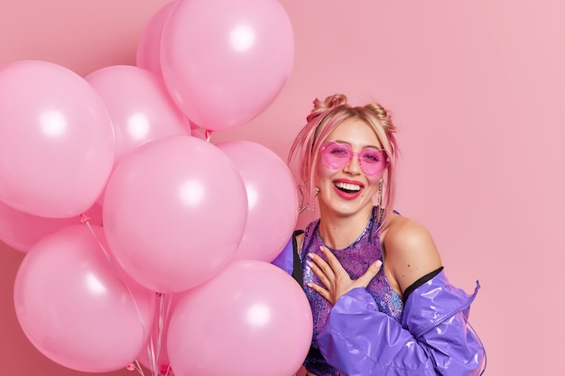 Positieve modieuze vrouw drukt oprechte emoties uit, glimlach voelt over het algemeen dankbaar