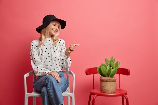 Positieve modieuze vrouw wijst naar ingemaakte cactus houdingen op stoel binnen