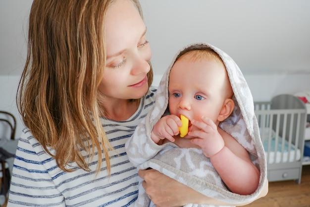 Positieve moeder die zoete, droge baby houdt die handdoek met een kap draagt na het douchen en rubberbadspeelgoed bijt. vooraanzicht. kinderopvang of baden concept