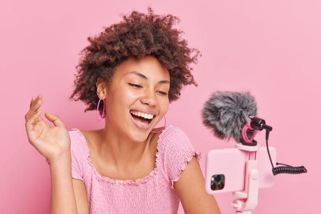 Positieve mooie brunette afro-amerikaanse vrouwelijke blogger gericht op smartphone op statief maakt online streaming heeft een eigen kanaal glimlacht graag poseert tegen roze muur. vlogconcept.