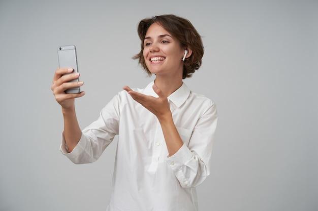 Positieve mooie brunette vrouw met kort kapsel foto van zichzelf maken met haar smartphone, breed glimlachen en gelukkig haar handpalm verhogen, geïsoleerd