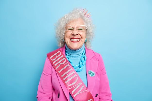Positieve mooie gerimpelde vrouw viert verjaardag, lacht tandjes heeft witte perfecte zelfs tanden draagt trendy kleding