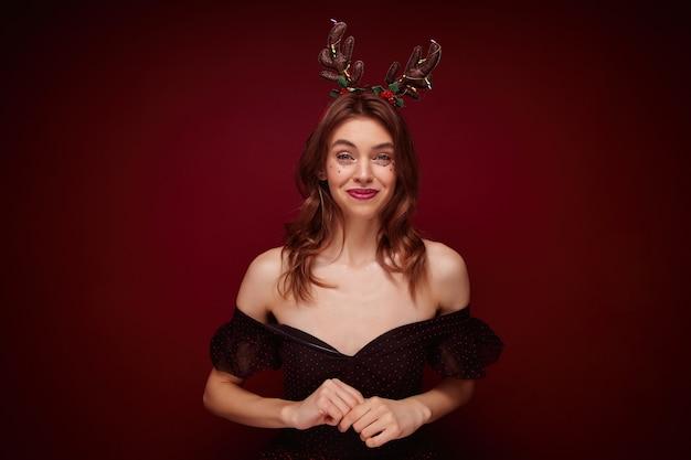 Positieve mooie jonge bruinharige vrouw, gekleed in elegante zwarte jurk met rode stippen terwijl je staat, verheugend leuk nieuwjaarsfeest samen met vrienden