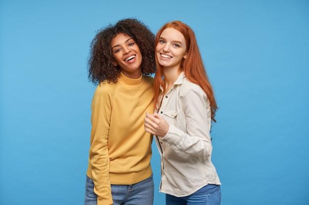 Positieve mooie jonge dames tonen hun witte perfecte tanden terwijl ze vrolijk kijken met een charmante glimlach, staande tegen een blauwe muur