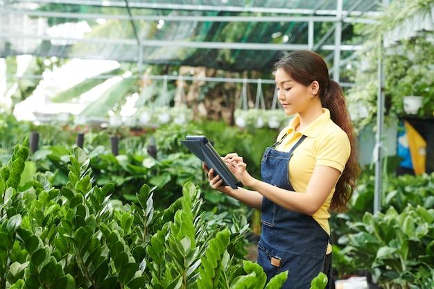 Positieve mooie jonge vrouw die op de plantenmarkt werkt en het aantal bestelde bloemen controleert