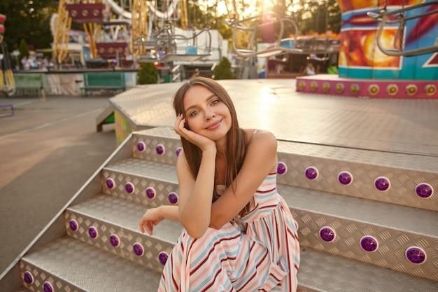 Positieve mooie jonge vrouw met bruin lang haar romantische lichte jurk dragen, zittend op trappen boven pretpark, hoofd leunend op haar handpalm en kijken met zachte glimlach