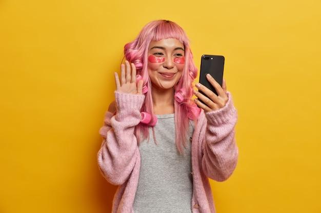 Positieve mooie jonge vrouw ondergaat schoonheidsprocedures, draagt rollers op geverfd roze haar, past collageen pads toe onder de ogen, maakt selfie met smartphone