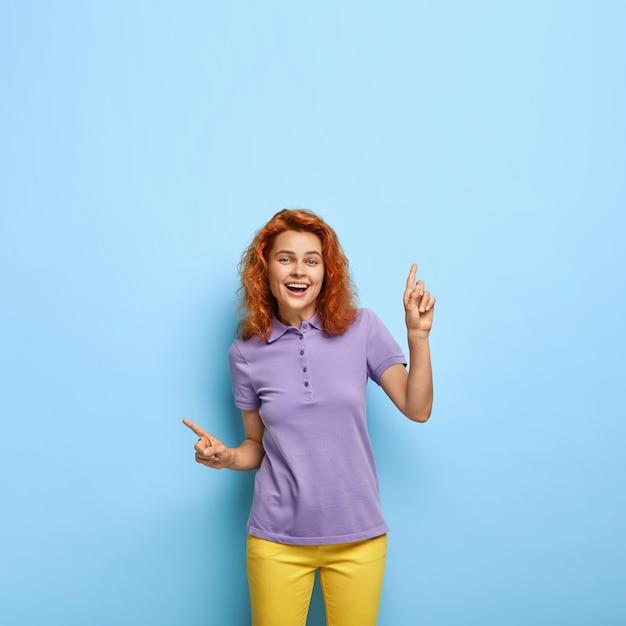 Positieve mooie roodharige gelukkige dame wijst zijwaarts, geeft geweldige aanbeveling