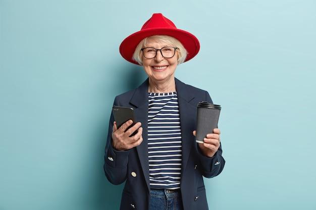 Positieve mooie roodharige vrouw in glazen, maakt gebruik van mobiele telefoon, stuurt bericht via multimediatoepassing, surft op sociale netwerken, heeft koffiepauze, houdt wegwerpkopje drank, geïsoleerd op blauw