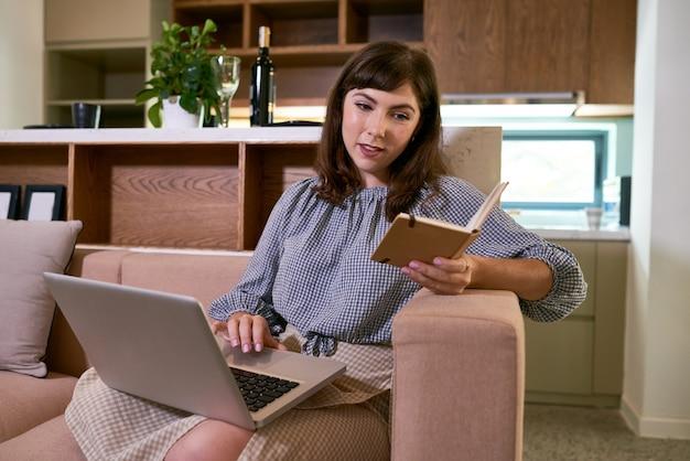 Positieve mooie vrouw die thuis op de bank zit, planner controleert en op laptop werkt, rekeningen betaalt of e-mails beantwoordt