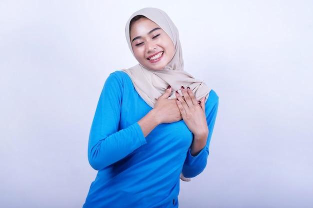 Positieve mooie vrouw houdt de handen op de borst, drukt dankbaarheid uit en glimlacht