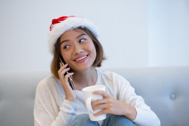 Positieve mooie vrouw in kerstmanhoed die op mobiele telefoon spreekt