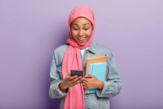 Positieve moslimvrouw kijkt naar smatphone-apparaat, draagt roze hijab, spijkerjasje