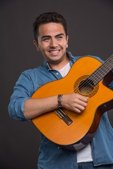 Positieve muzikant gitaarspelen op zwarte achtergrond
