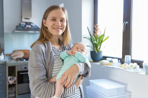 Positieve nieuwe moeder die vrolijke baby schommelt
