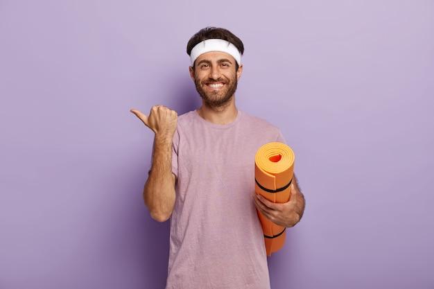 Positieve ongeschoren man draagt witte hoofdband en paars t-shirt, houdt opgerolde mat vast, wijst opzij