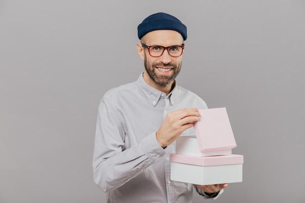 Positieve ongeschoren man heeft stoppels, draagt dozen met cadeau, opent er een van