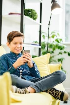 Positieve ontspannen schooljongens zittend op de gele bank met gekruiste benen en glimlachen tijdens het gebruik van een moderne smartphone