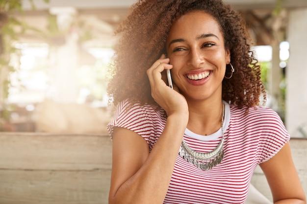 Positieve ontspannen vrouw heeft telefoongesprek