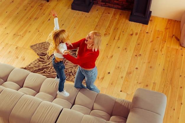 Positieve opgetogen blonde vrouw speelt met haar dochter