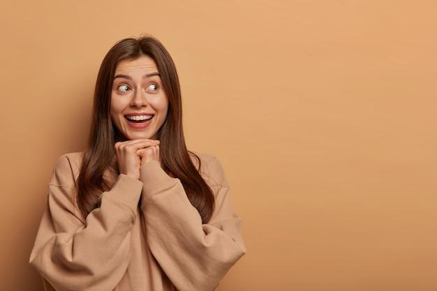 Positieve opgetogen vrouw kijkt graag opzij, heeft een tedere glimlach, houdt beide handen onder de kin, heeft een aantrekkelijk uiterlijk, draagt een sweatshirt