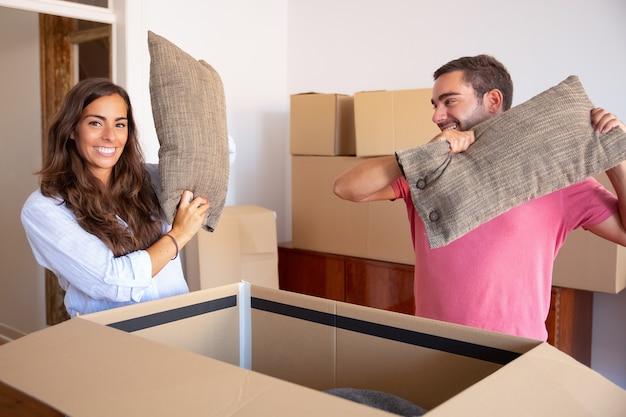 Positieve opgewonden jonge man en vrouw die kussens van open kartonnen doos uitstappen, genieten van het verplaatsen en uitpakken van dingen