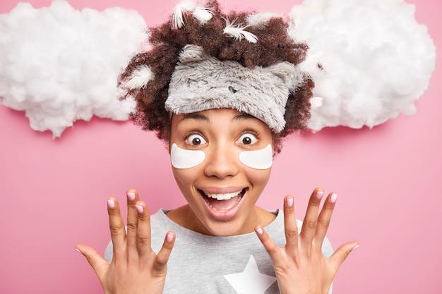 Positieve opgewonden vrouw met krullend haar steekt handen op glimlacht heeft gelukkig verbaasd uitdrukking veren vast in haar draagt slaapmasker nachtkleding wordt verrast door geweldig nieuws geïsoleerd over roze muur