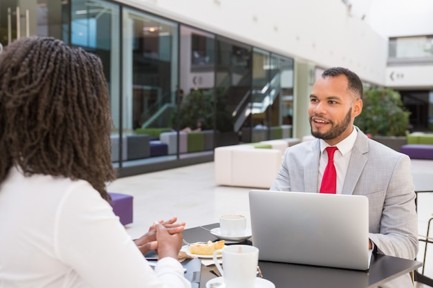 Positieve opgewonden zakenman chatten met collega