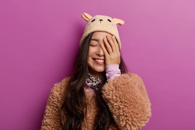 Positieve oprechte jonge vrouw lacht van vreugde, bedekt de helft van het gezicht, houdt de ogen gesloten, gekleed in winterse bovenkleding