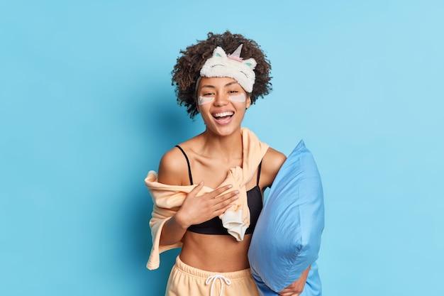 Positieve oprechte vrouw met krullend haar draagt gezichtsmasker zachte pyjama lacht gelukkig wenst u welterusten geïsoleerd over blauwe muur