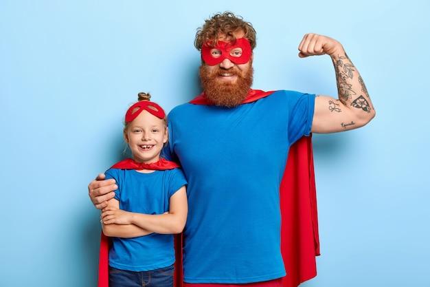 Positieve optimistische papa heft getatoeëerde arm op, toont spieren
