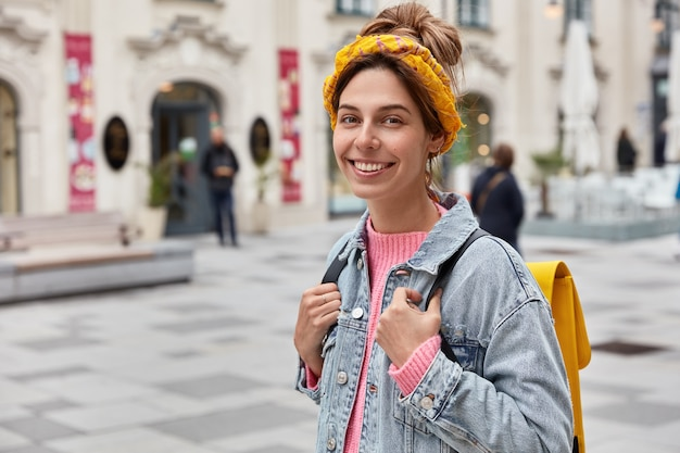 Positieve optimistische vrouw heeft een vrolijke uitdrukking, draagt stijlvolle kleding, heeft een gele kleine rugzak op de rug, dwaalt door de straten van de stad