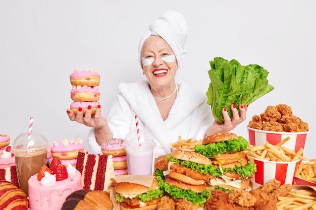 Positieve oude gerimpelde vrouw glimlacht vrolijk en kiest tussen groene slasalade en donuts