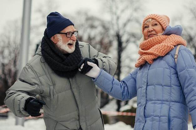 Positieve oude man en vrouw in winterkleren lachen en hand in hand terwijl ze het evenwicht bewaren op de ijsbaan