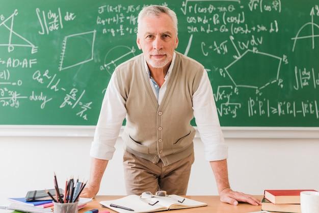 Positieve oude wiskundeleraar die op bureau leunt