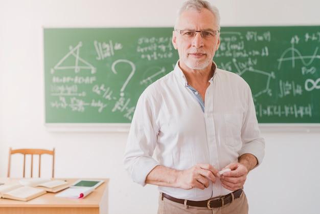 Positieve oude wiskundeleraar die zich met krijt bevindt