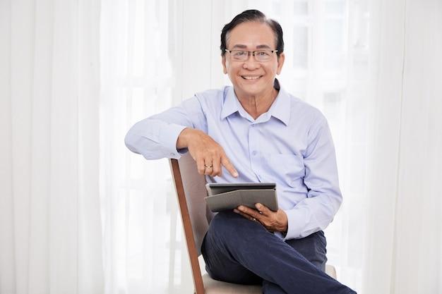 Positieve oudere man die op een stoel zit en nieuws leest of sociale media controleert op tabletcomputer