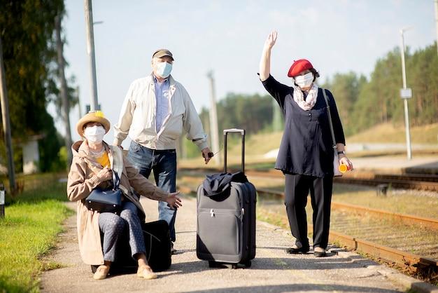 Positieve oudere senioren met gezichtsmaskers die trein wachten voordat ze op reis gaan