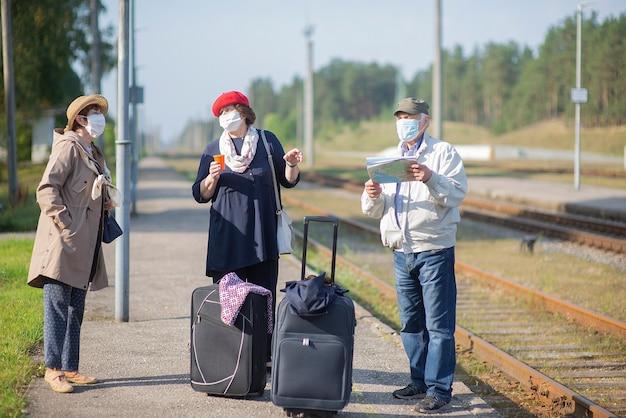 Positieve oudere senioren met gezichtsmaskers die wachten op de trein voordat ze reizen tijdens een covid-19-pandemie