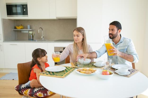 Positieve ouders en dochter zitten aan de eettafel met schotel, fruit en koekjes, sinaasappelsap gieten.