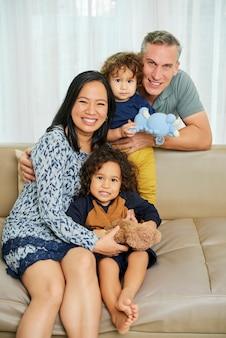 Positieve ouders en hun twee zonen die thuis op de bank rusten en naar de camera glimlachen