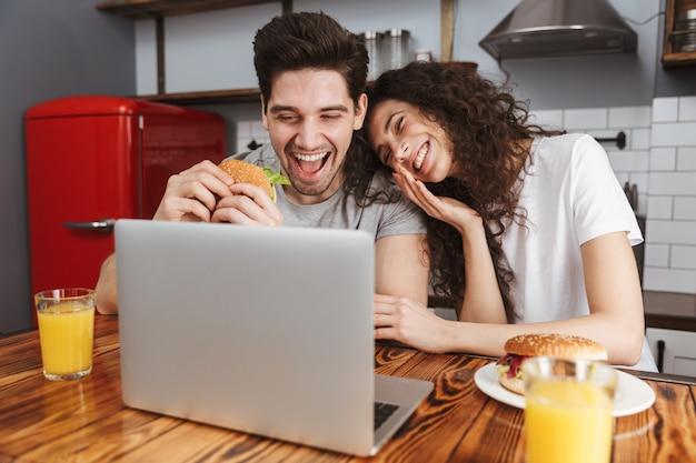 Positieve paar man en vrouw kijken naar laptop op tafel terwijl ze thuis hamburger eten in de keuken