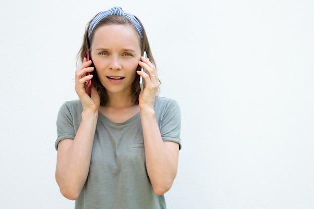 Positieve peinzende jonge vrouw die op twee telefoons spreekt