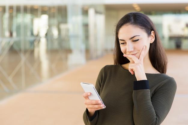 Positieve peinzende latijnse vrouw met cellphone wat betreft gezicht