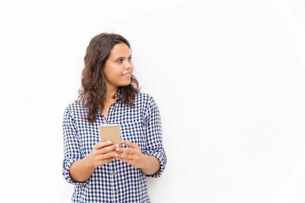 Positieve peinzende latijnse vrouw met cellphone