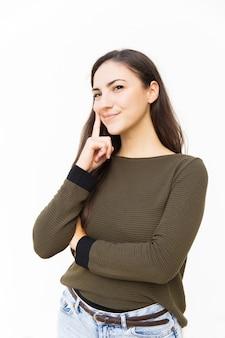 Positieve peinzende vrouwelijke vrouw wat betreft gezicht met vinger