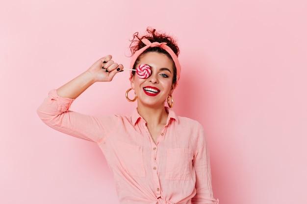 Positieve pin-up girl met rode lippenstift in roze outfit en gouden oorbellen met lolly.
